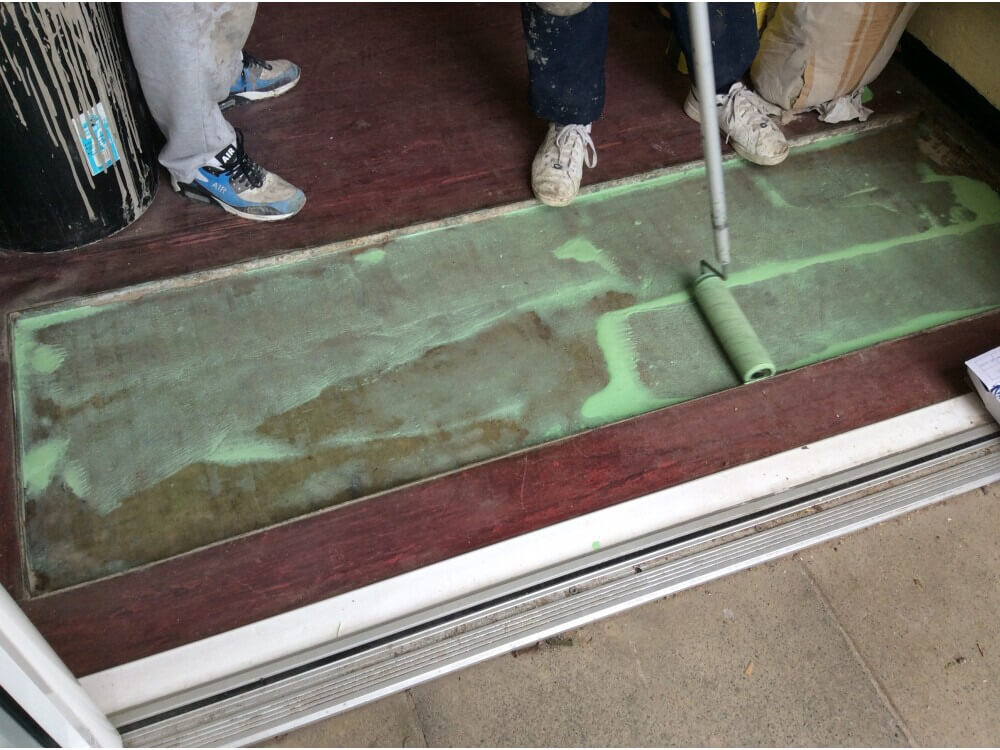 Matwell having primer applied