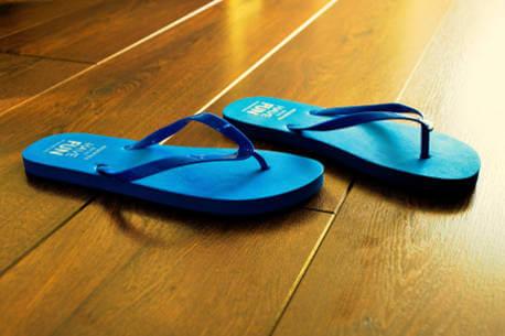 blue-flip-flops-on-wooden-floor